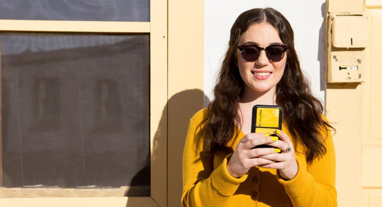 woman-wearing-yellow-sweater-looking-at-phone-smiling