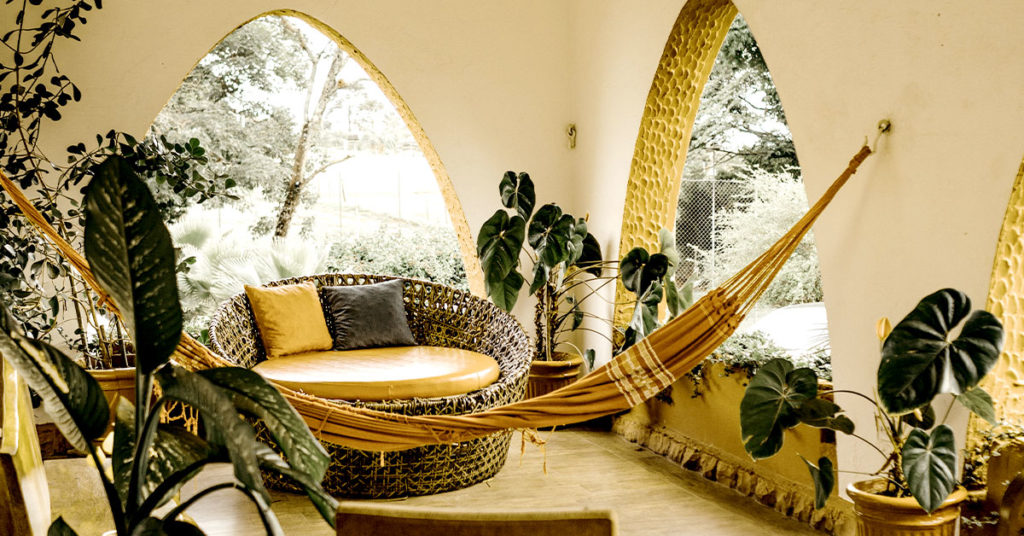 Indoor/outdoor space with rattan chair and hammock